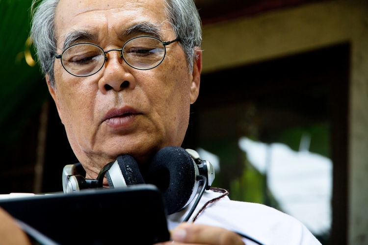 Close-up of senior man using mobile phone