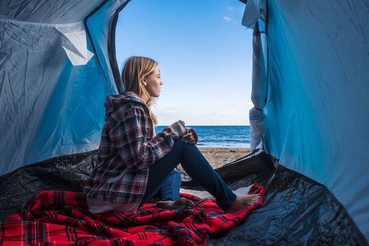 lifestyle for blonde beautiful woman outside her tent near the ocean Camping Adult Beauty In Nature Blond Hair Blue Sky Coffee Cup Day Full Length Horizon Over Water Leisure Activity Lifestyles Nature One Person Outdoors People Scenics Sea Serene People Sitting Sky Vacations Water Women Young Adult Young Women