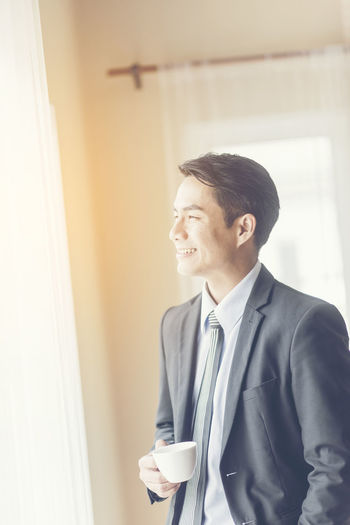 Side view of businessman drinking coffee while standing by window at home