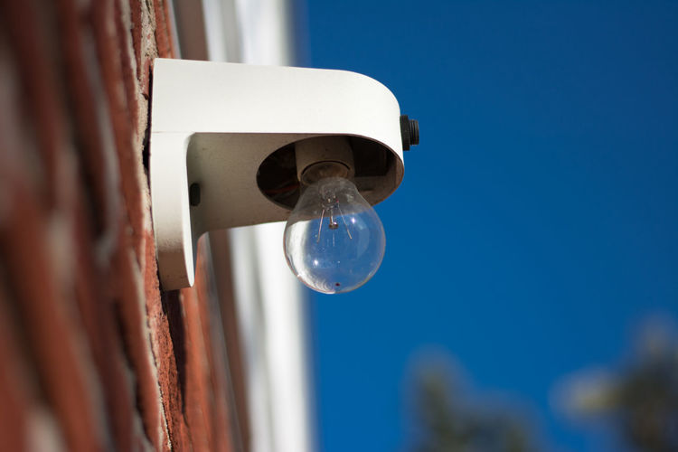 Low angle view of light bulb mounted on brick wall against clear blue sky