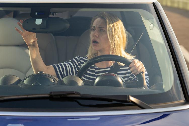 Woman looking down in car