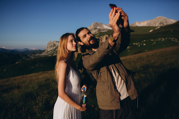 Young woman using smart phone while standing on mountain