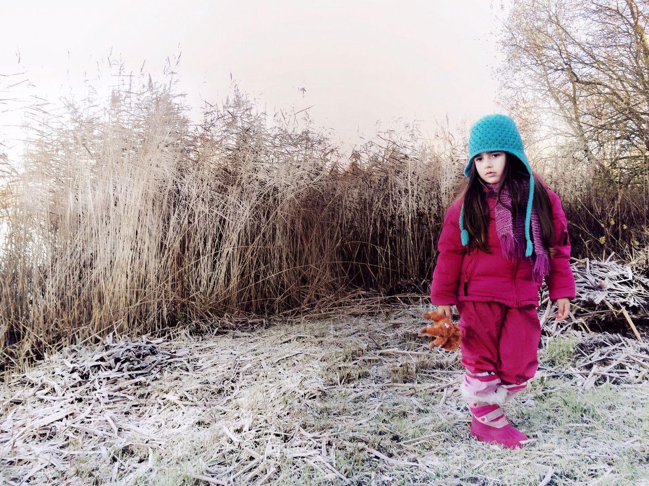 Full length of girl holding teddy bear and walking on grassy field