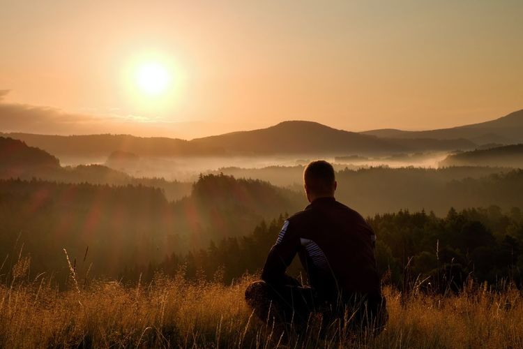 Hiker in squatting position in high grass meadow enjoy the colorful sunrise scenery