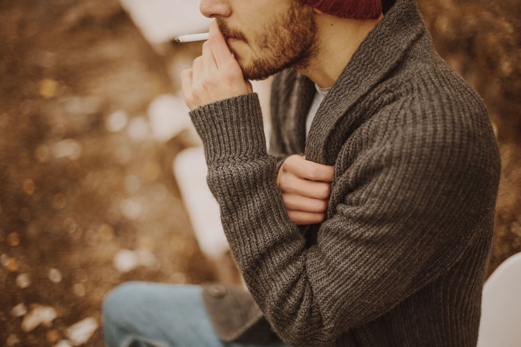 Midsection of young man smoking cigarette while sitting outdoors