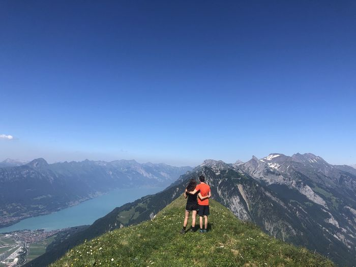 Rear view of couple on mountain against clear blue sky