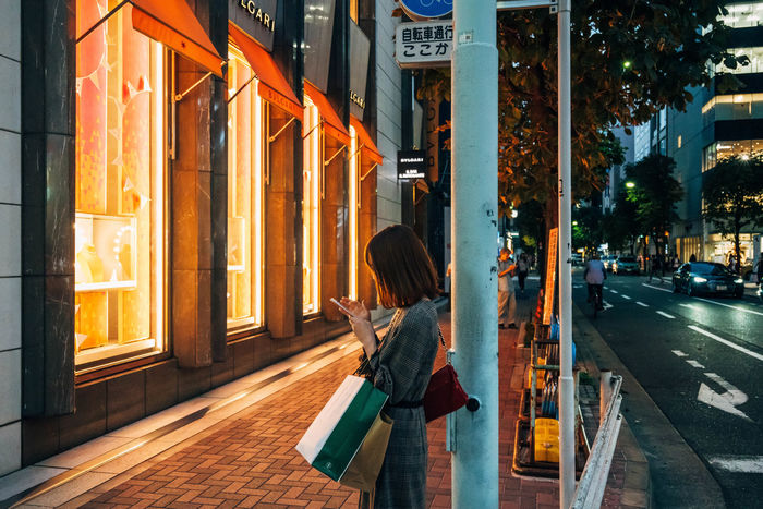 Architecture City Building Exterior Street Real People Built Structure Illuminated One Person Road City Life Transportation Lifestyles Incidental People Walking Women Adult Rear View Orange Color Sidewalk Outdoors