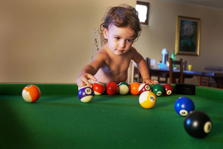Girl playing with snooker balls on pool table