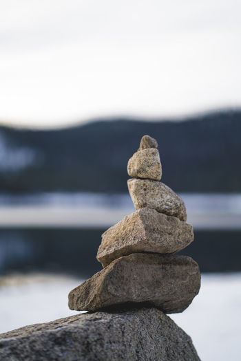 Close-up of stone stack on rock at beach against sky