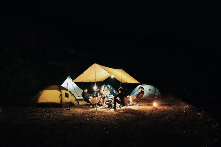 Camping Tent Night Friendship Adventure Men Lifestyles Medium Group Of People Leisure Activity Illuminated Enjoyment Togetherness Vacations Outdoors Real People Sand Sitting Bonfire Shelter Women