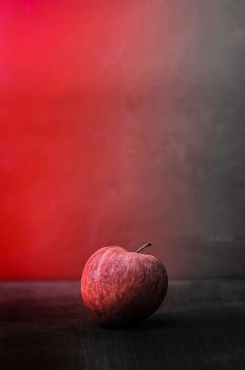 Close-up of apple on table against red background