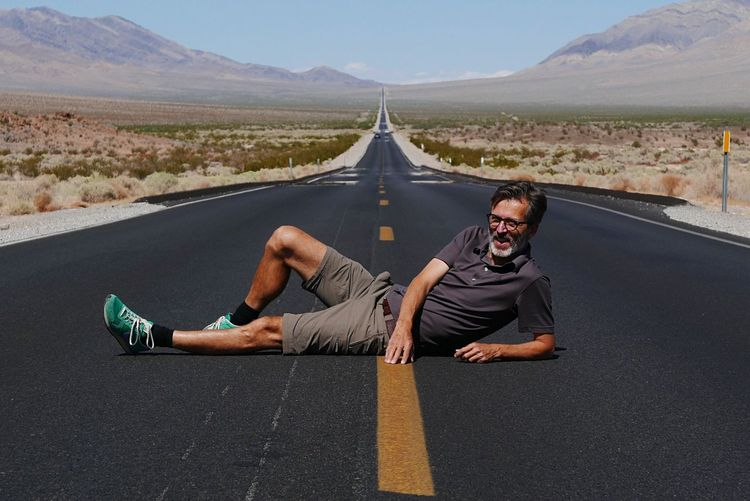 Mature Man Lying On Road Against Sky