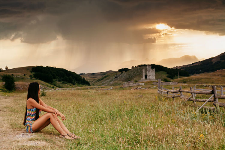 Woman relaxing at countryside with rain at sunset view in Montenegro. Long hair girl sitting and look on rain. Beautiful Nature Females Green Lifestyle Rain Relaxing Travel Travel Photography Vacations Woman Beautiful View Beautiful Woman Girl Long Hair Montenegro Mountain Nature One Person Outdoors Picturesque Real People Sexygirl Summer Sunset Travel Destinations