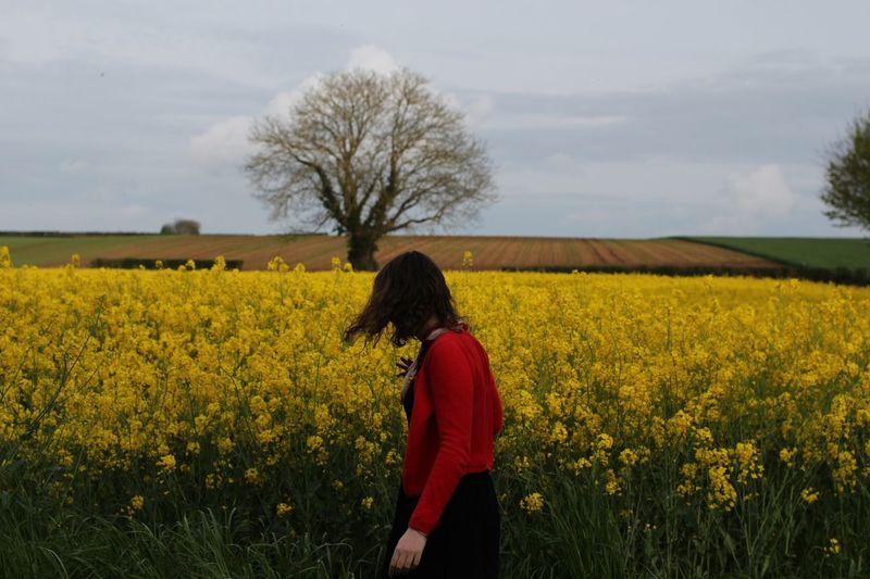 Woman Standing In Rapeseed Field
