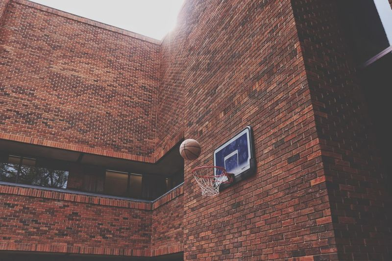 Low Angle View Of Ball Falling In Basketball Hoop Attached On Brick Wall