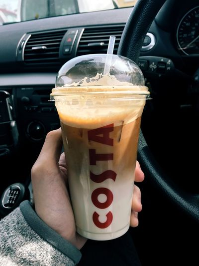 A person is pictured holding a Costa Coffee Iced latte take away cup up inside a BMW car