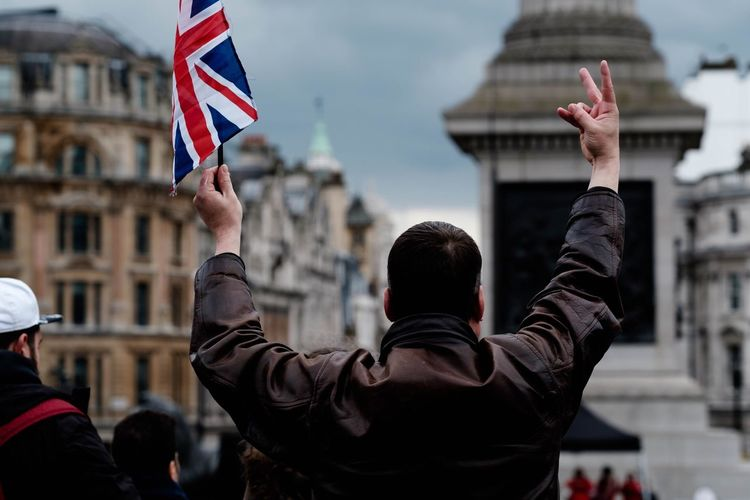 Rear View Of A Man Holding British Flag