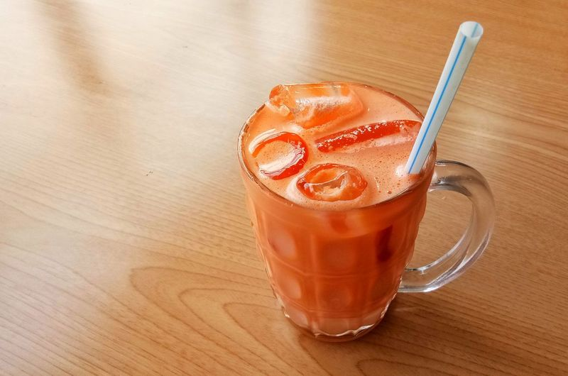 Carrot milk iced on wooden table Vegetable Drink Orange Color Cool Drink Diet Diet Drink Frothy Drink Drink Drinking Glass Cafe Table Sugar Ice Cube