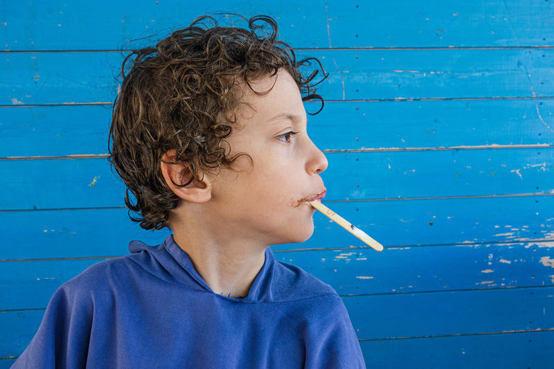 Close-up of boy eating popsicle looking away against blue wall