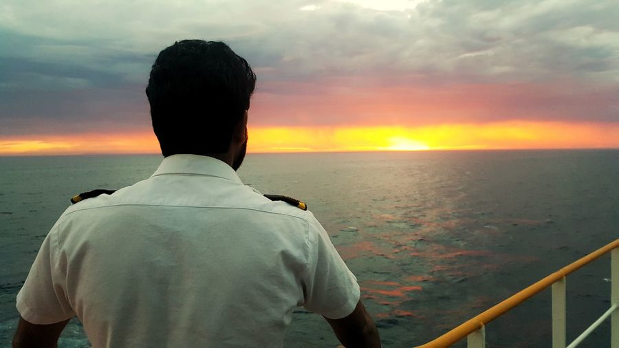 Rear View Of Male Navy Officer On Boat In Sea During Sunset