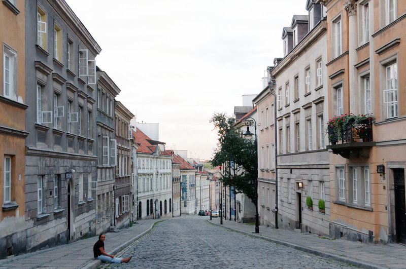 Man Sitting On Footpath Against Buildings In City