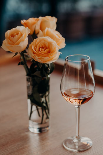 Close-up of wine with rose vase on table