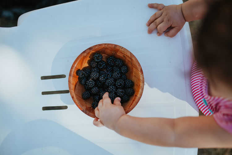 Directly above shot of baby girl picking blackberry from bowl