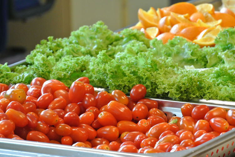 Close-up of tomatoes and lettuce in container for sale