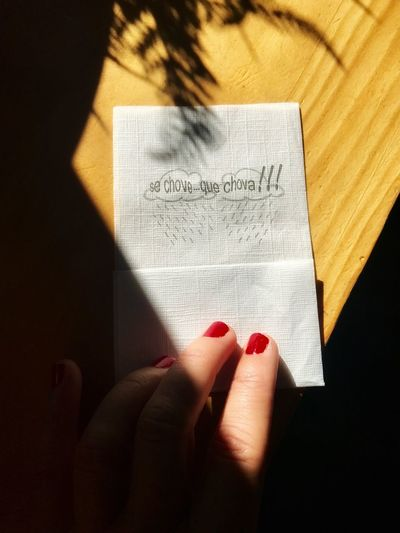 Cropped hand holding paper with text on wooden table