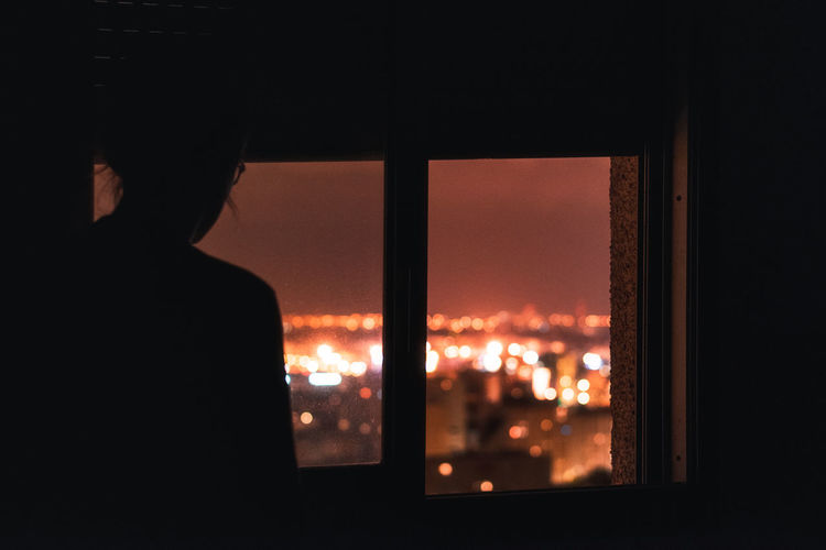 Window One Person Silhouette Real People Indoors  Illuminated Transparent Lifestyles Architecture Rear View Dark Night Glass - Material Built Structure Looking Leisure Activity Men Looking At View Contemplation City Lights