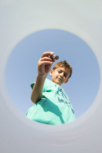 Low angle view portrait of boy holding blue sky