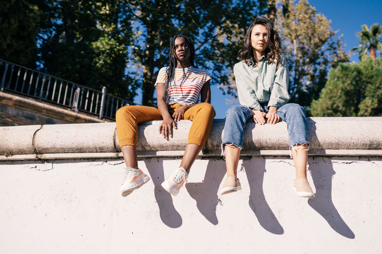 Low angle view of friends sitting on retaining wall