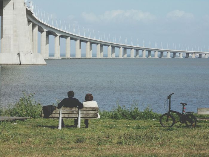 Rear View Of Couple Sitting On Bench At Tagus Riverbank