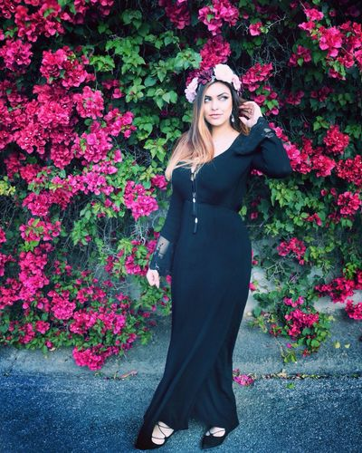 Full length of thoughtful young woman standing against pink flowering trees