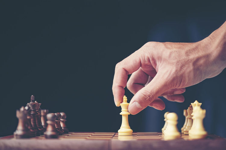 Arts Culture And Entertainment Black Background Board Game Chess Chess Board Chess Piece Competition Finger Game Hand Human Body Part Human Hand Human Limb Indoors  King - Chess Piece Knight - Chess Piece Leisure Activity Leisure Games Men One Person Playing Queen - Chess Piece Relaxation Sport Strategy