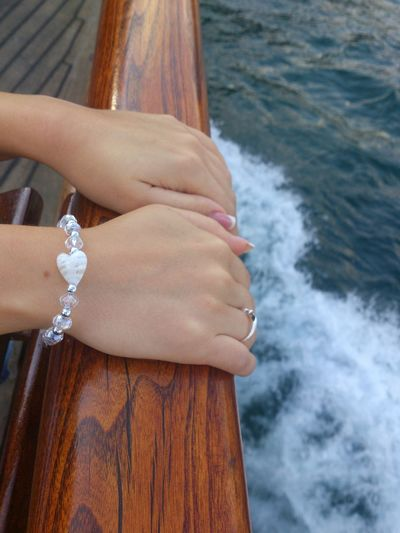 Cropped hands of woman on railing against sea