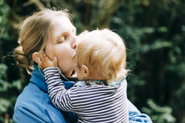 Close-up of mother kissing son