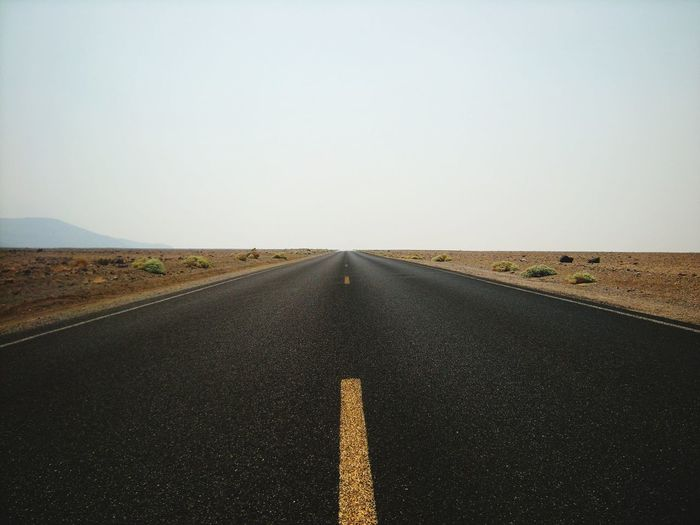 Diminishing perspective of empty road against clear sky