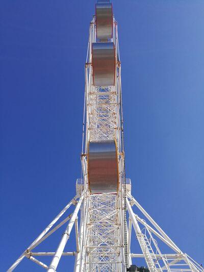 Directly below shot of ferris wheel against clear blue sky