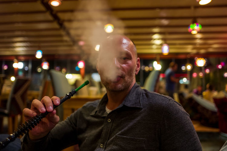 Portrait of man smoking hookah in bar