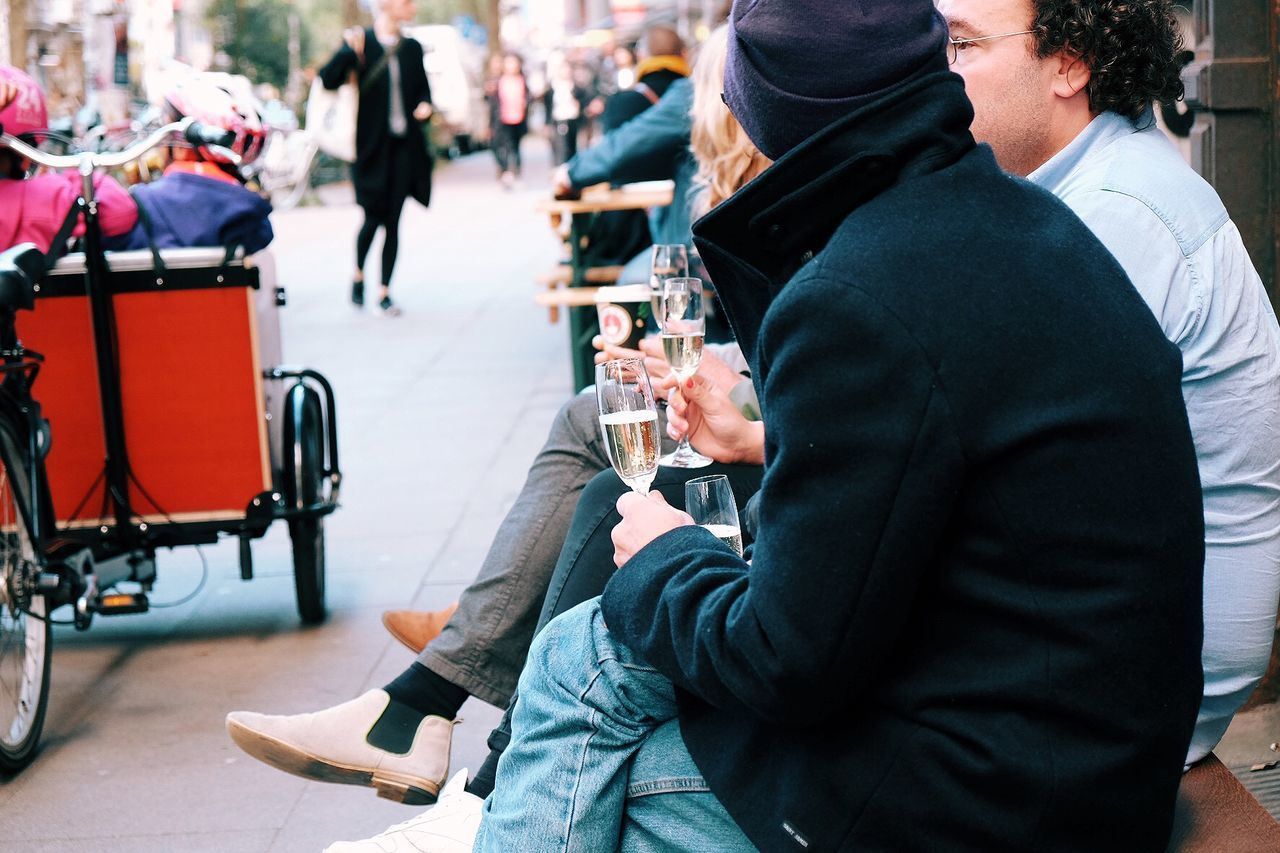 People sitting on bench with champagne by street