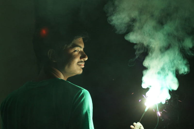 Rear view of man holding sparkler during night