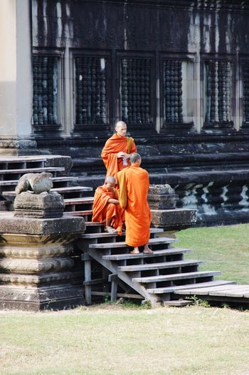 Buddhist monks Architecture Sitting Standing Stairs Steps Religious  Spirituality EyeEmNewHere Men Adults Architecture Khmer Cambodia Angkor Wat Ancient Civilization Ruins Ancient Temple Orange Orange Robes Robes Buddhism Buddhist Monks Young Monks Monks Architecture Religion Belief Spirituality Place Of Worship