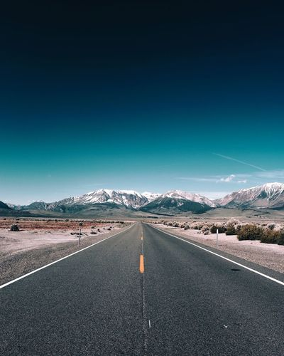 Empty road leading towards mountains against sky during winter