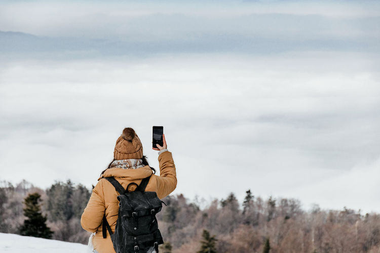 Rear view of young woman standing on top of hill and taking photos of valley. winter, fog.