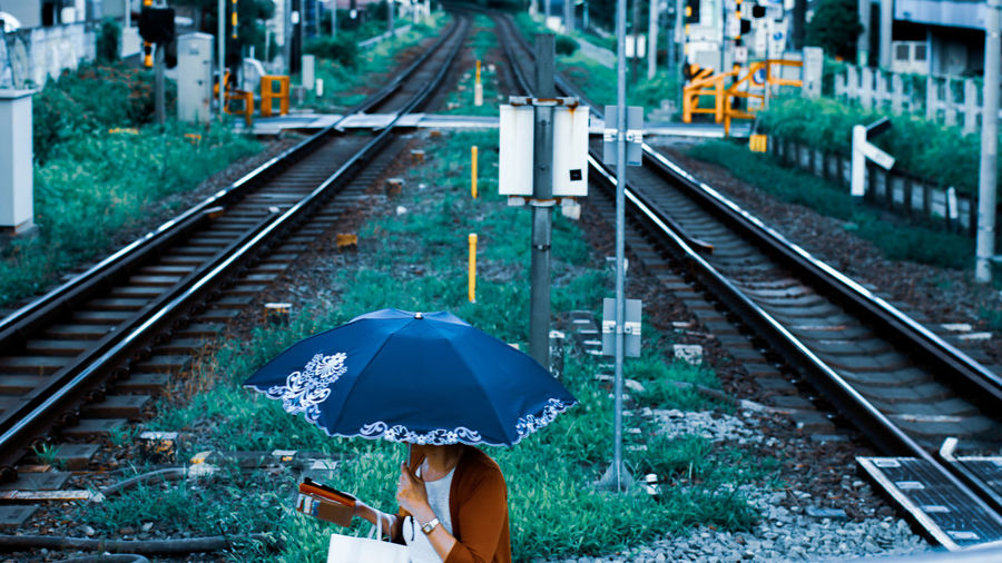Blue umbrella on railway The Portraitist - 2018 EyeEm Awards Railroad Track Rail Transportation Railroad Station Platform Railroad Station High Angle View Umbrella Railway Signal The Photojournalist - 2018 EyeEm Awards The Great Outdoors - 2018 EyeEm Awards