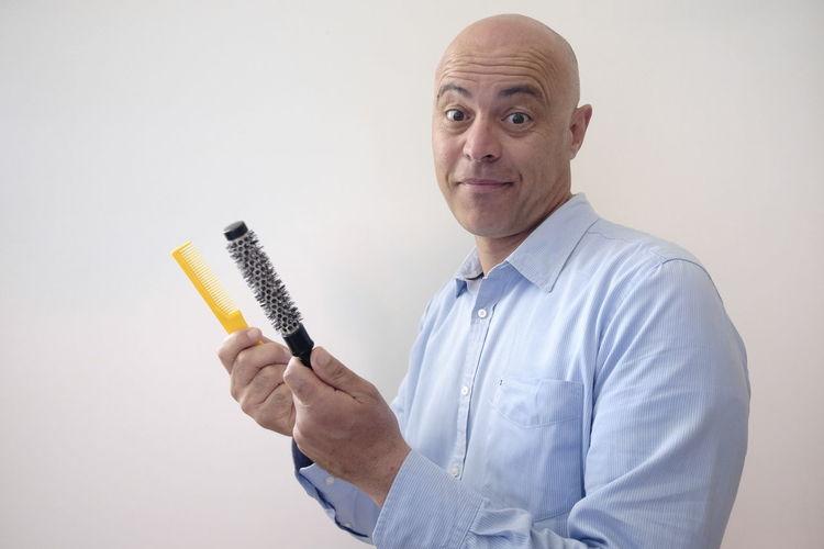 Portrait Of Smiling Bald Man Holding Comb