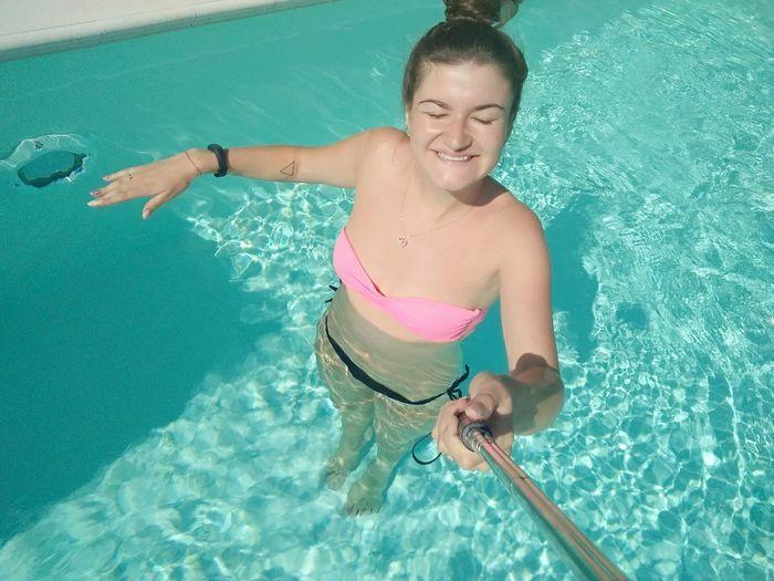 High Angle View Of Woman Wearing Bikini Taking Selfie From Monopod In Swimming Pool On Sunny Day