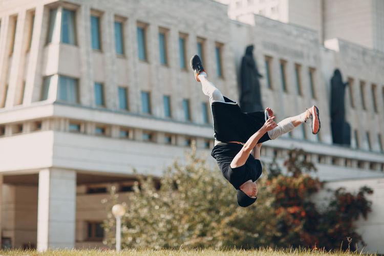 Full length of man jumping against building