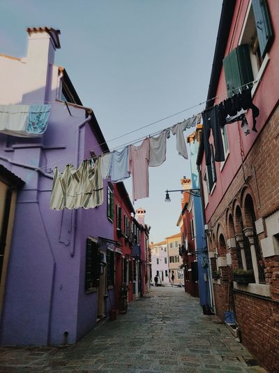 Clothes drying on alley amidst buildings against sky
